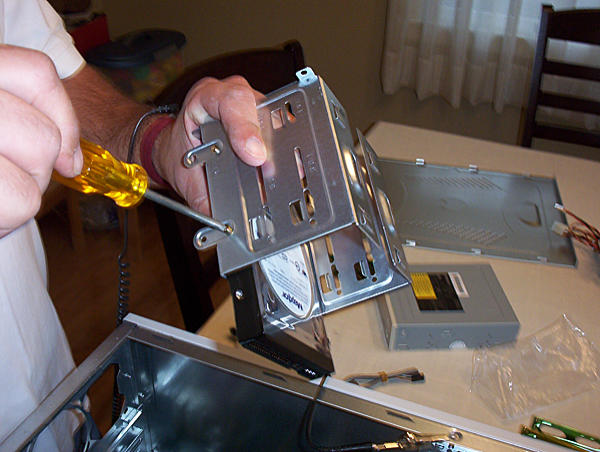 Physically installing the hard drive into the hard drive cage using a screwdriver