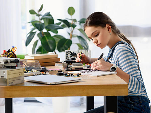Teen girl with computer parts and a notebook